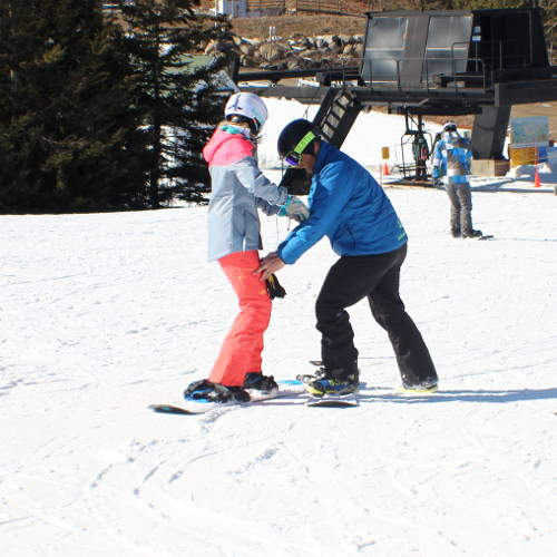 A snowboard instructor and student working together.