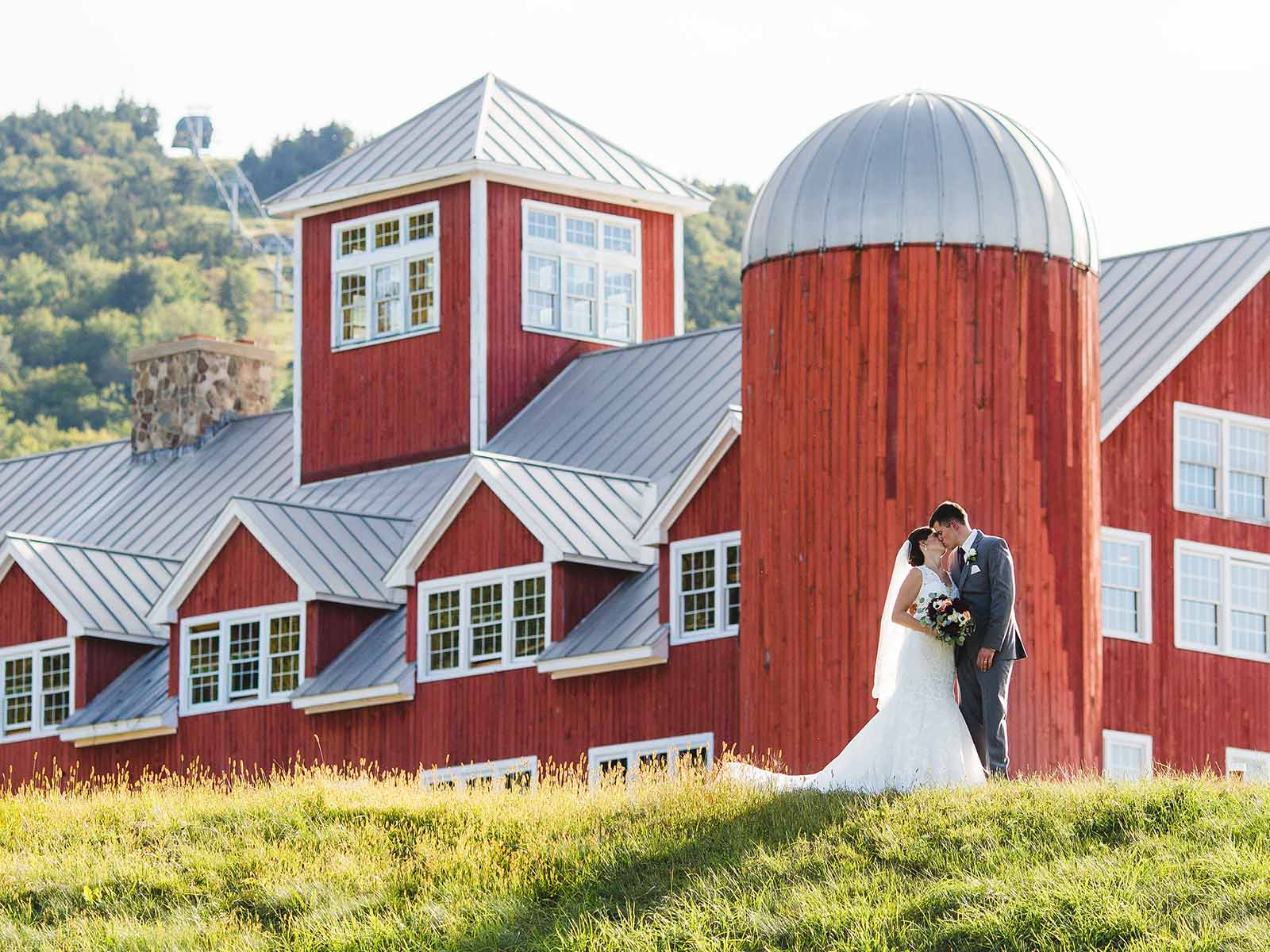 A bride and groom in front of the Red Barn silo.